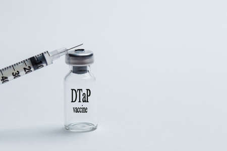 Vaccine from diphtheria, tetanus and whooping cough in a vial and a syringe on a white background