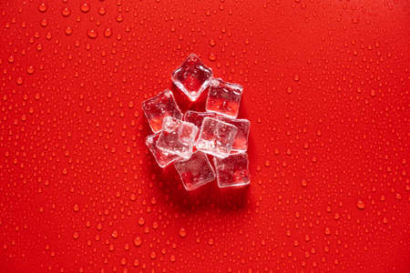 Ice cube with water drops on a red background Stock fotó