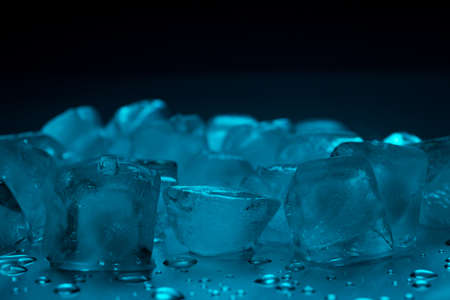 Ice cubes in turquoise color on a black background with drops of water Stock fotó