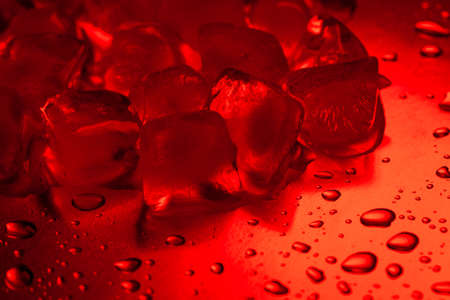 Red ice cubes on a reflecting table with drops of water close-up