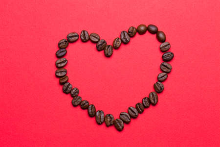 Grains of coffee in the form of heart on a red background