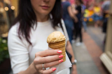 Girl holding ice cream closeup in hand