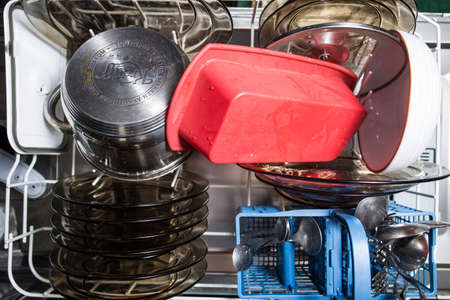Kiev, Ukraine - March 27, 2021: Dishwasher with dirty dishes closeup. Household kitchen appliances. Assistant hostess.