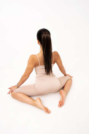 Girl doing stretching in the studio on a white background. A beautiful gymnast with a flexible body and athletic uniform.