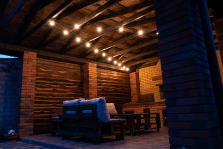 Barbecue area in the evening with antique light bulbs. Furniture made of wood and pallets.