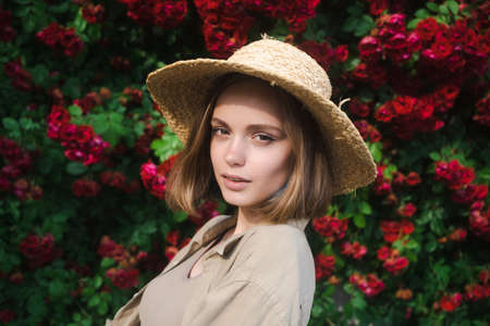 Elegant beautiful blonde young woman in a straw hat on the background of a bush of blooming roses.