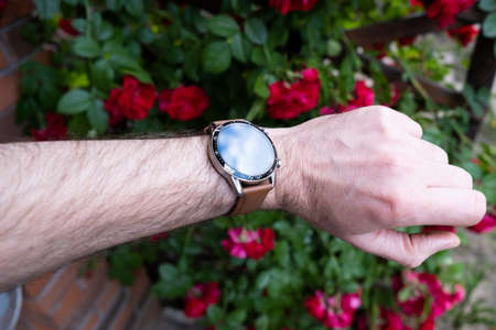 Smart watch on a mans hand against a background of red flowers. Stock fotó