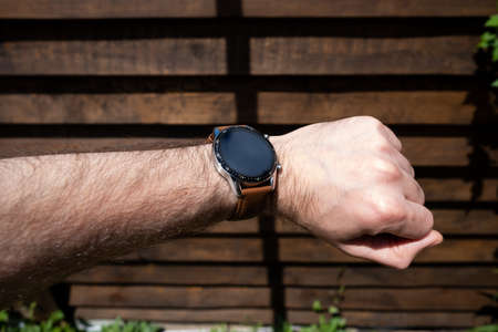 Smart watch on a mans hand on the background of a wooden fence.
