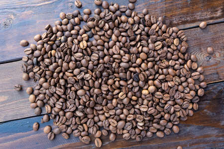 Roasted coffee grains on a wooden table close-up.