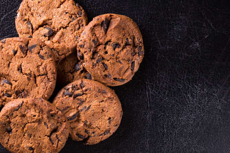 Appetizing chocolate chip cookies with slices of raisins on a black background.