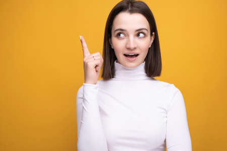 The girl in the studio on a yellow background raised her thumb up with an idea of emotion. Stock fotó