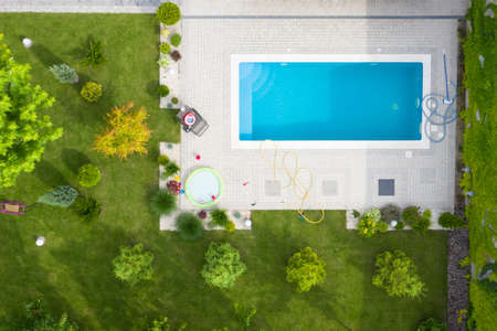 Aerial shot of green lawn and garden with a swimming pool in the courtyard.