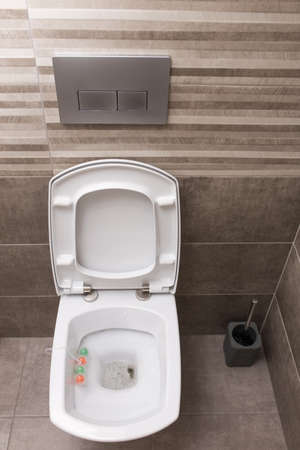 New white ceramic toilet on a gray tile background. The interior of the restroom. Stock fotó