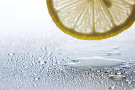 Slice of lemon on a steel reflective background with water drops close-up Stock Photo