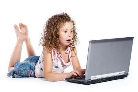 The beautiful girl of 7 years lying surprised near the laptop on a white background photo