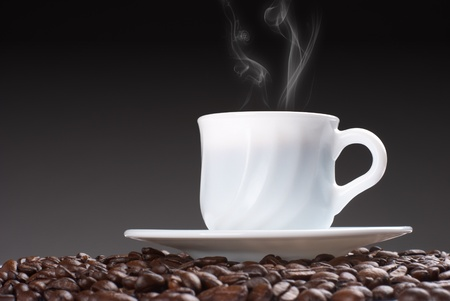 Cup of hot drink with steam on the coffe beams photo