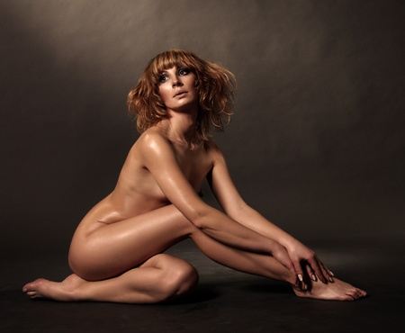 nude woman sitting: The beautifull nude woman on black background Stock Photo