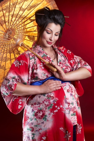 Beautiful pregnant geisha with umbrella photo