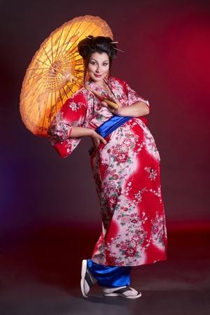 Beautiful pregnant geisha with umbrella photo