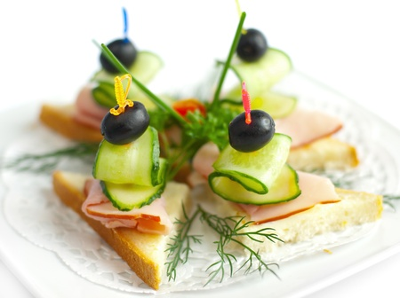 Close-up canape with ham, cucumbers and olive
