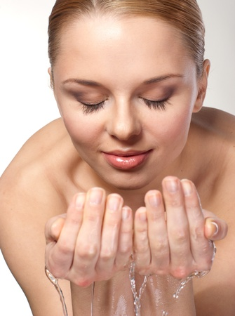 Close-up portrait of a cute young woman wash her face with water Stock Photo