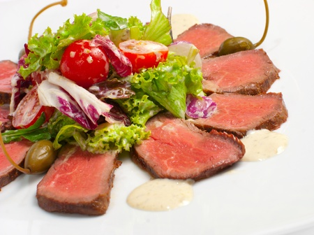 roasted meat with salad and tomato