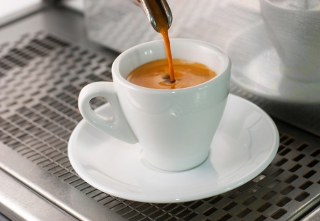 coffee machine: Espresso pours out of a group head into a coffee shot glass.