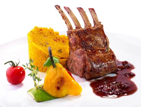 rack of lamb with vegetables and couscous on white background