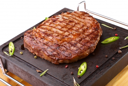Rib-eye steak resting on the hot stone plate Imagens