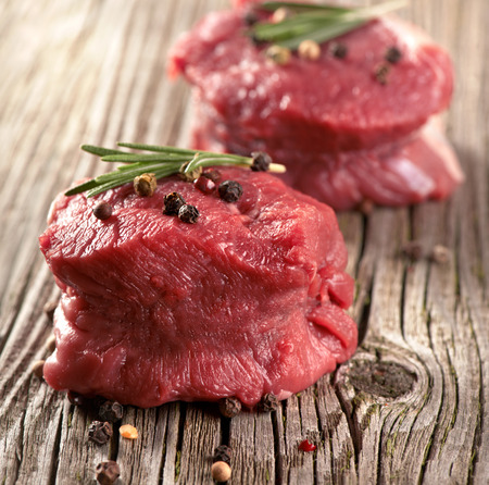 steak cru: steak cru avec du poivre sur bois