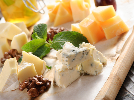 emmental: Assorted cheese on a wooden board with honey
