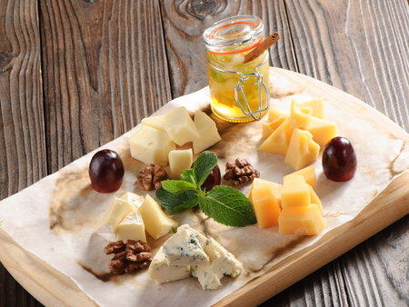 parmesan cheese: Assorted cheese on a wooden board with honey