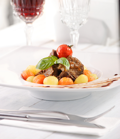 Beef cheek with vegetables on white