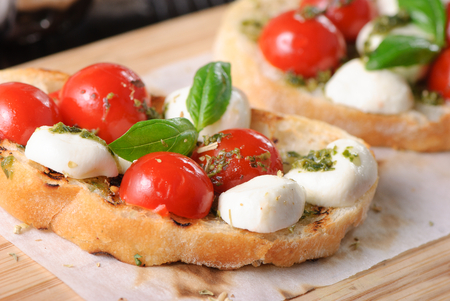 bruschetta Caprese on the wooden plate Imagens