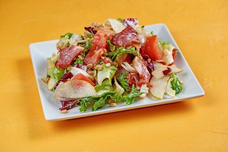 Salad with pear, proshutto, grapes, arugula, soft cheese and nuts. Salad of autumn Stock Photo