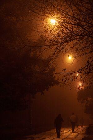 Gente caminando por la noche en la niebla. Foto de archivo