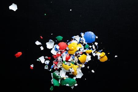 smithereens: Broken colored egg shells on black background