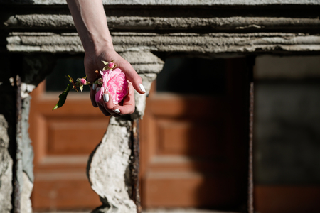 garden statuary: Girl holding a flower on the backdrop of the collapsed railings