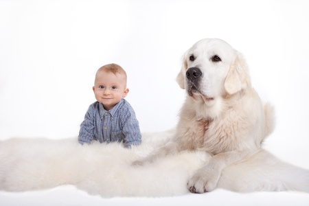 Eigth months old baby and his dog lying on belly and smiling to the camera photo