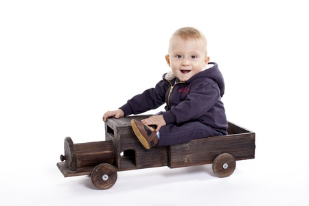 Baby boy playing with a wooden car photo