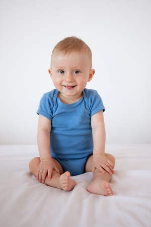 9 months old: 9 months old baby boy sitting on a bed and smiling Stock Photo