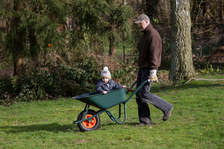Boy and his dad working together in the garden photo