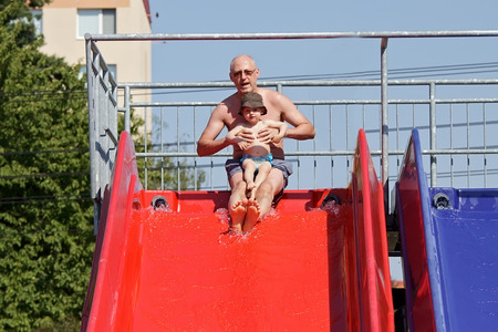 Father and son on water slide  photo