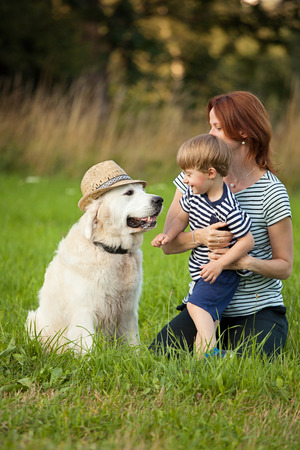 Mom, son and dog having fun with hat photo