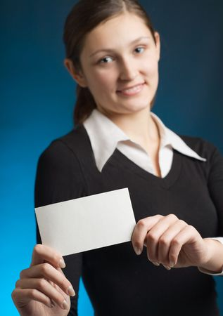 affability: Young secretary or businesswoman with blank notecard, smiling. Focus on card