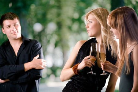 Two women holding glasses with champagne and laughing, young man looking at them and smiling, outdoors, focus on women photo