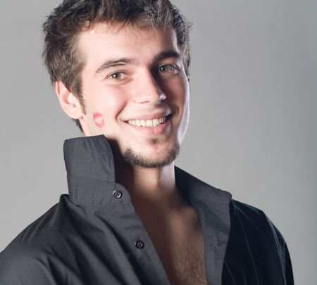 Young man with lipstick kiss, smiling photo