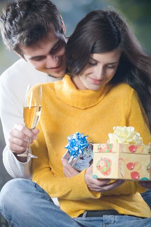 Young happy couple celebrating event with champagne and gift boxes, outdoor photo