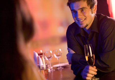 Young couple sharing champagne glasses in restaurant, celebrating or on romantic date. Focus on man. Stock Photo - 802635