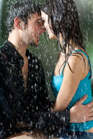 Young couple hugging and smiling under a rain, in passion Stock Photo - 802641